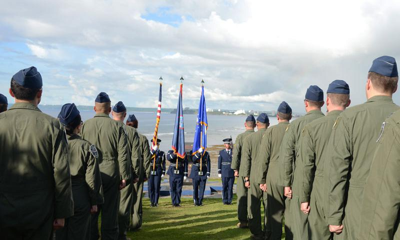 Airmen from the 20th Expeditionary Bomb Squadron currently deployed to Andersen from Barksdale Air Force Base, Louisiana, stand at attention for the Guam Hymn during the Raider 21 memorial ceremony July 21, 2015, in Adelup, Guam.  (U.S. Air Force photo by Airman 1st Class Ariel Vasquez)