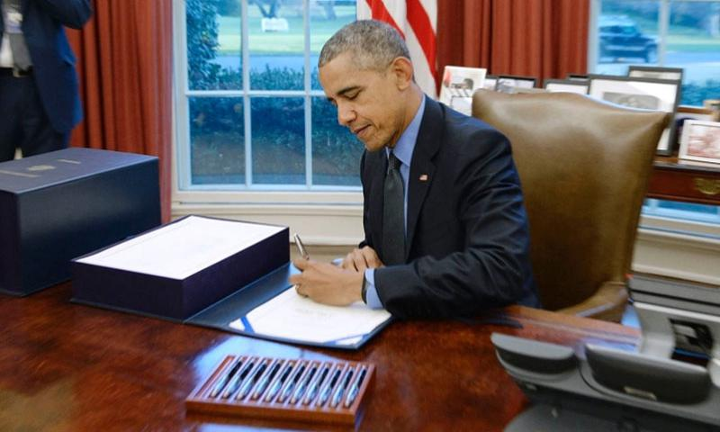 US President Barack Obama signs a compromise $1.1 trillion spending package that funds the government through next September in the Oval Office at the White House on Dec. 18, 2015 in Washington, D.C.   Olivier Douliery, Abaca Press/TNS