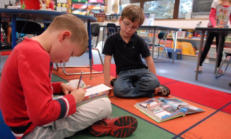 "Zachary Smith, left, and Nicholas Von Eicken, second-graders at Ramstein Elementary School take turns reading and answering questions about a story during a ""cooperative buddy"" reading activity. The Department of Defense Education Activity is investing much time and money into its early literacy program, including implementing a new time-intensive reading assessment for more than 30,000 students in kindergarten through third grade."