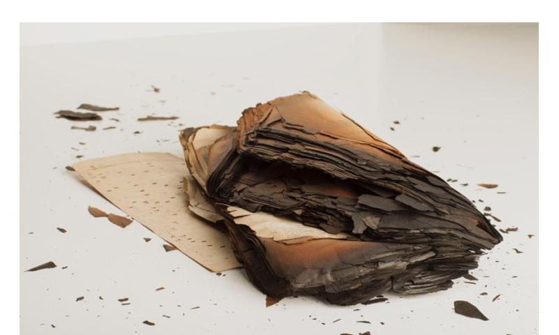 Technicians with the National Personnel Records Center in St. Louis work to recover as much information as they can from burned clumps of documents such as this one. COURTESY OF NATIONAL ARCHIVES AND RECORDS ADMINISTRATION