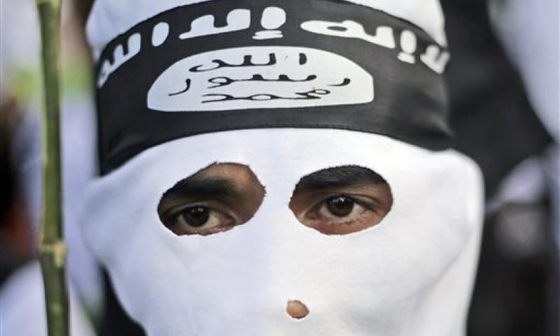 In this June 18, 2014 photo, a Muslim man wears a headband showing the Islamic State group's symbol during a protest calling for the closure of a local prostitution complex in Surabaya, Indonesia. The world's largest Muslim country is facing a new threat as security officials fear that militants who are joining the Islamic State could take part in terrorism acts on their return to Southeast Asia. Dita Alangkara/AP