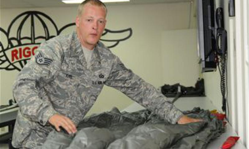 Staff Sgt. Christopher Kitts, 36th Operations Support Squadron aircrew flight equipment specialist flattens out the folded parachute prepping it for the final pack.