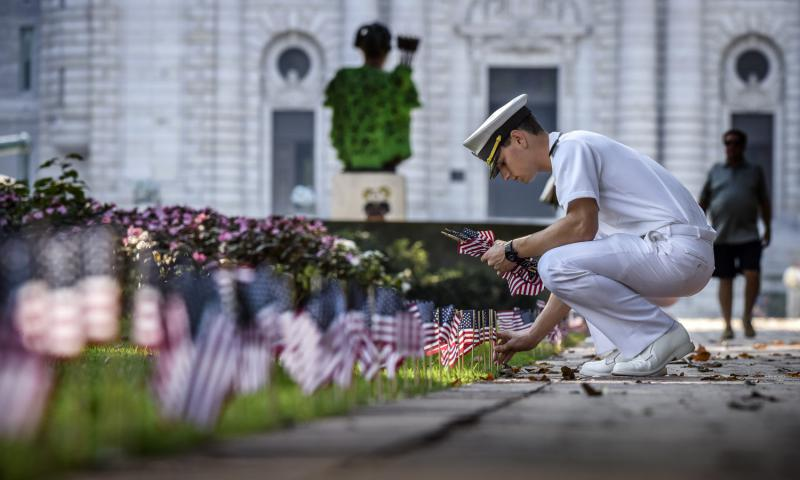 Midshipman Shawn Picciott places one of 2,996 flags on Stribling Walk, representing those lost in 9/11, at the U.S. Naval Academy in Annapolis, Maryland. Bill O'Leary/Washington Post