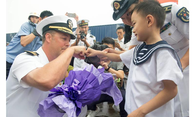 Cmdr. Justin Harts, commanding officer aboard the Arleigh Burke-class guided-missile destroyer USS Benfold (DDG 65), greets a child and receives a bouquet of flowers from members of the People's Liberation Army   Photo by Mass Communication Specialist 3rd Class Deven Leigh Ellis