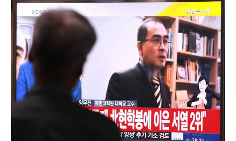 """A man watches a TV news airing a file image of Thae Yong Ho, minister at the North Korean Embassy in London, at Seoul Railway Station in Seoul, South Korea, Wednesday, Aug. 17, 2016. Thae has defected to South Korea, becoming one of the highest Northern officials to do so, South Korea said Wednesday. The letters read """"He was the No. 2 man at the embassy."""" Ahn Young-joon/AP Photo"""