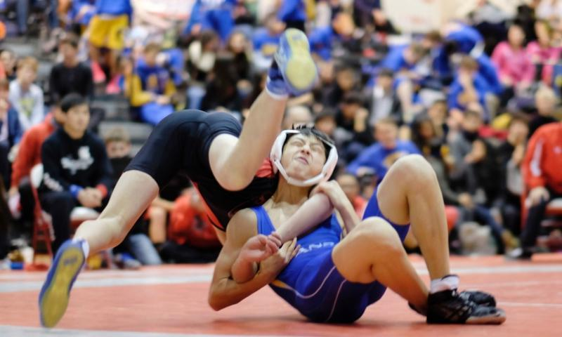 St. Mary's Chang Young Lee tosses Nile C. Kinnick's Calvin Mull over his shoulder in the 108-pound championship of the Beast of the East wrestling tournament.   James Kimber/Stars and Stripes