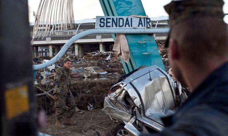 Marine Corps Staff Sgt. Hugo Roman from Camp Fuji assists in the clearing of the airport in Sendai, Japan, after it was severly damaged after the 9.0 earthquake and resulting tsunami hit the area on March 11, 2011. U.S. forces cleared the runway of hundreds of wrecked cars and other debris enabling the airport to receive humanitarian aid.    Stars and Stripes