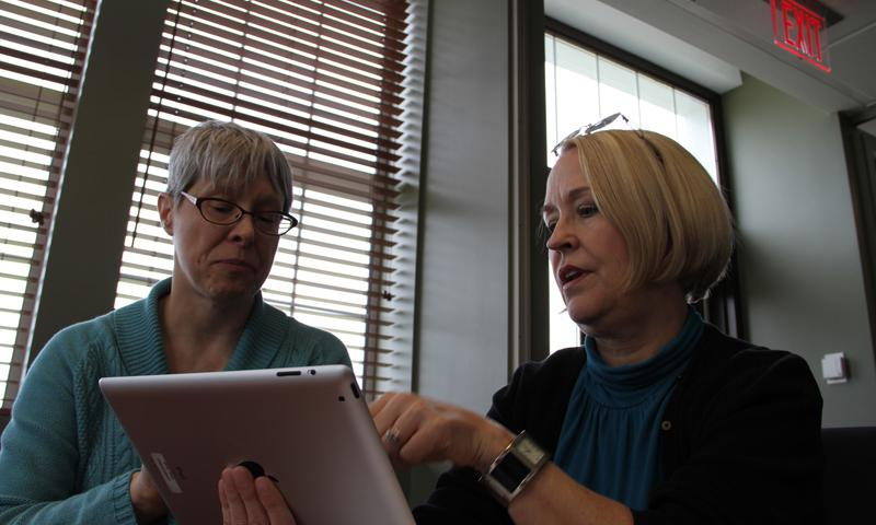 """Dr. Kelly Blasko and team member Julie Holland discuss """"The Big Moving Adventure,"""" a mobile app to help children of military families moving to a new location. DOD photo courtesy of the National Center for Telehealth and Technology"""