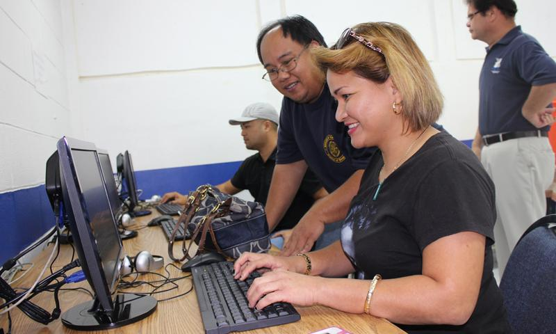 Vice Mayor Rudy Iriarte shows Priscilla Fernandez of Yona how to access the KeyTrain training component of WorkKeys, the Job Assessment and Training program offered through GCC, at the Community Access Point that opened at the Sinajana mayor's office on Sept. 5.