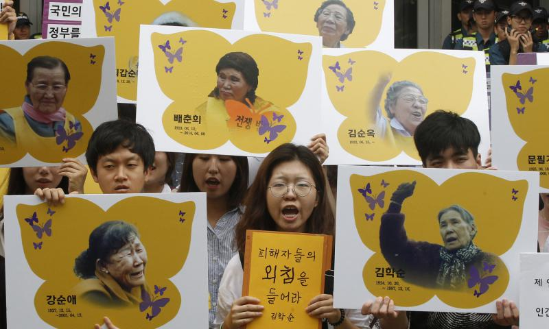 Protesters hold portraits of former South Korean sex slaves who were forced to serve Japanese troops in World War II, during a rally against the establishment of the Japanese government-funded Reconciliation and Healing Foundation in Seoul, South Korea, in July 2016. 	 Ahn Young-joon, File/AP