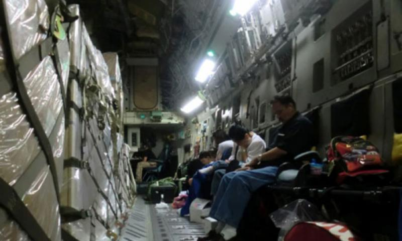 Sharing the space with pallets full of equipment, Space-A passengers rest aboard a C-17 aircraft bound for the U.S. from Japan. Photo by Tim Wightman/Stars and Stripes