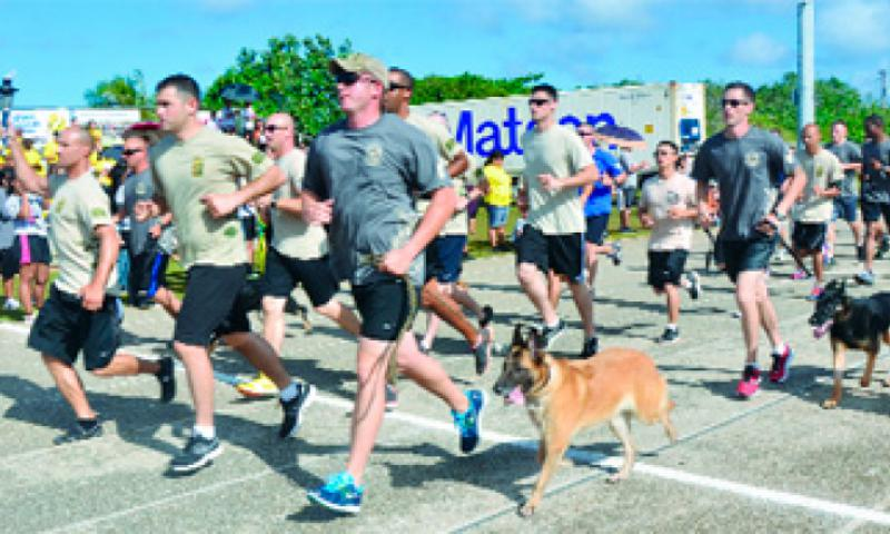 Members from the 736th Security Force Squadron run with the torch during the 37th Annual Special Olympics of Guam Track and Field event at Okkodo High School in Dededo, Guam, March 23.