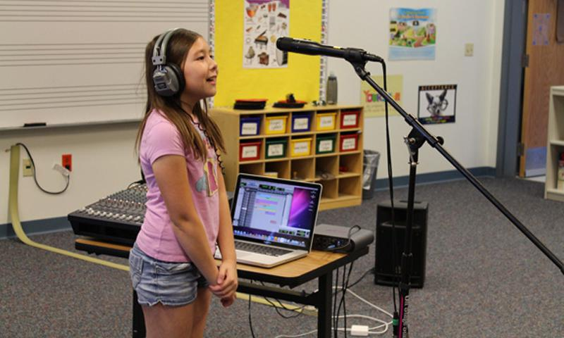 "Santa Rita, GUAM (21 Dec. 2013) — McCool Elementary/Middle School fifth-grader Stella German records a song during the making of a video for the White House Student Film Festival. Her film entitled ""We Will Raise a Ruckus Tonight"" was selected from among 2000 nationwide entries for the final round of competition at the White House on Feb. 28, 2014 (Released/Photo courtesy of Nicholas Trosclair)"