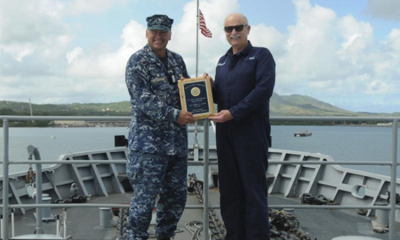SANTA RITA, Guam (June 29, 2016) Capt. Mark A. Prokopius, commanding officer of the submarine tender USS Emory S. Land (AS 39), left, and Military Sealift Command Civilian Mariner Michael S. Flanagan, officer-in-charge aboard the Emory S. Land, right, pose on the forecastle of Emory S. Land, showcasing a newly received plaque after winning the Fiscal Year 2015 Chief of Naval Operations Environmental Quality Award for the Afloat 2015 Military Sealift Command category.