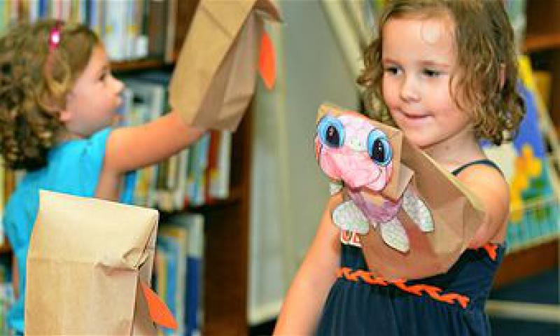A child plays with a puppet she made during story time at the base library Aug. 7, 2013, on Andersen Air Force Base, Guam. Every story time begins with singing a song, followed by the story, finishing with the related activity. Story time is held every Wednesday from 3 to 4 p.m. at the Andersen Library. For more information, call 366-4291. (U.S. Air Force photo by Airman 1st Class Mariah Haddenham)