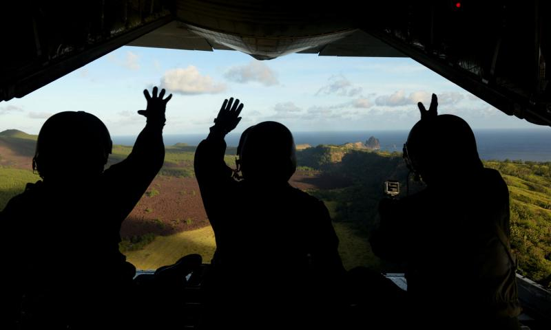 apan Air Self-Defense Force airmen wave at residents of Pagan island in the Commonwealth of the Northern Mariana Islands after dropping a package to the islanders as part of Operation Christmas Drop. Community members and an environmental group on Wednesday, July 27, 2016, sued the U.S. Navy, the Department of Defense and the secretary of defense over a plan to turn two Pacific islands, including Pagan, into live-fire testing sites. Benjamin Gonsier/U.S. Air Force photo