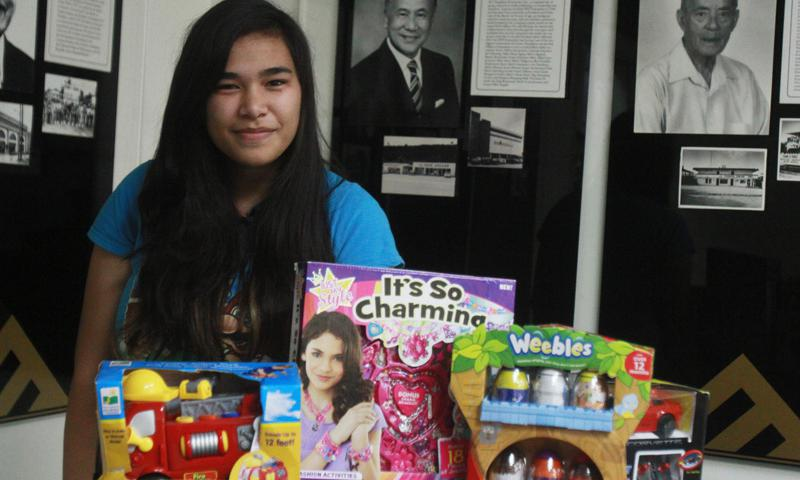 Noah Martin, a native of Santa Rita, Guam, stands with her donation of gifts to Toys for Tots at the Guam Chamber of Commerce Offices.  Martin, a 16-year-old junior at Southern Christian Academy, asked family and friends for gifts for Toys for Tots at her 16th birthday party in-lieu of presents for herself.  Her generous act resulted in a donation of more than 60 items to the Guam Toys for Tots campaign.  (Official US Marine Corps photo by Sgt. John Raufmann)