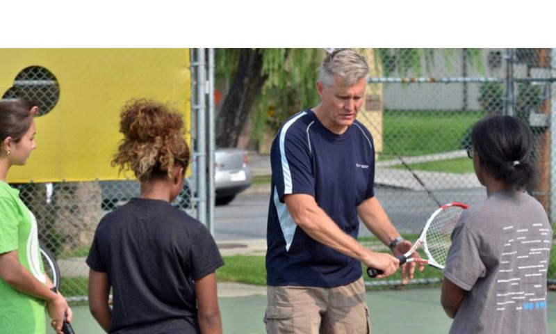 Daegu tennis coach Brett Leonard passes some pointers to girls players Irene Halferty, Armyll Smith and Jade Stokes. Dave Ornauer/Stars and Stripes