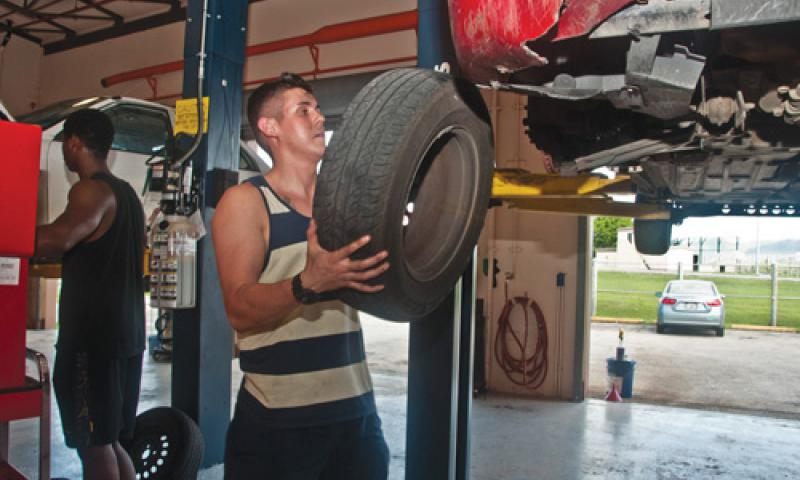 USS Frank Cable (AS 40) Engineman 3rd Class (SW) Joseph Reeves prepares to mount his tire at the Auto Hobby Shop on U.S. Naval Base Guam Nov. 16. The shop provides a facility for patrons to repair and maintain their privately-owned vehicles while fostering automotive skill building. U.S. Navy photo by Shaina Marie Santos