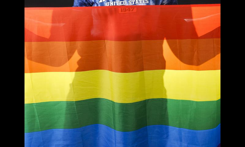 A U.S. airman holds a rainbow flag for Lesbian, Gay, Bisexual, and Transgender Pride Month during a June 12, 2014, event at Eielson Air Force Base, Alaska. 	 Ashley Nicole Taylor/U.S. Air Force