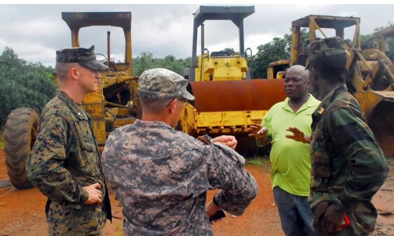 Marine Lt. Col. Doug Woodhams, U.S. Army Africa Sgt. Bromley and Liberian armed forces Capt. Abraham Karmara discuss construction details with a Liberian contractor at the future location of an Ebola treatment unit near Barclayville, Liberia, on Oct. 11, 2014.  Craig Philbrick/U.S. Army
