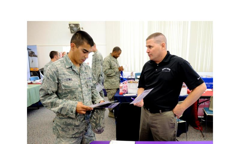 An airman speaks with a Grand Canyon University representative at an education fair at Vandenberg Air Force Base, Calif., Aug. 16, 2012.   U.S. Air Force, Flickr