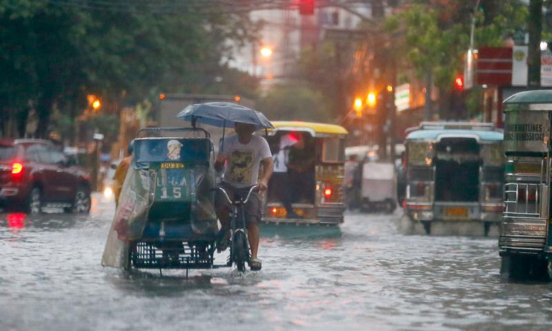 In this Aug. 26, 2016 file photo, commuters and motorists go on their way as heavy monsoon rains inundate low-lying areas in Manila, Philippines. Typhoons that slam into land in the northwestern Pacific _ especially the biggest tropical cyclones of the bunch _ have gotten considerably stronger since the 1970s, a new study concludes. Bullit Marquez/AP Photo, File