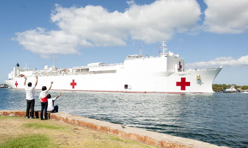 Onlookers wave to the Military Sealift Command hospital ship USNS Mercy as it arrives at Joint Base Pearl Harbor-Hickam on May 25, 2015.