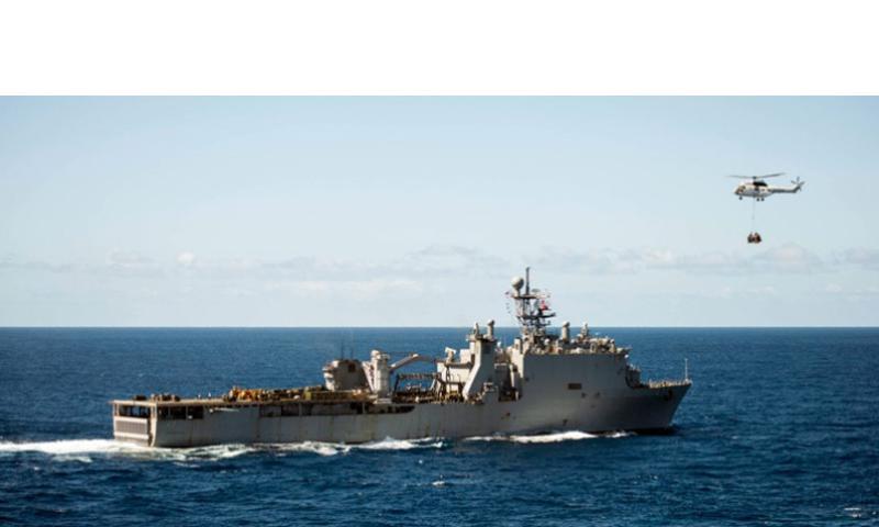 A helicopter flies near the dock landing ship USS Germantown while underway in the western Pacific Ocean in August 2013.    Edward Guttierrez III/U.S. Navy