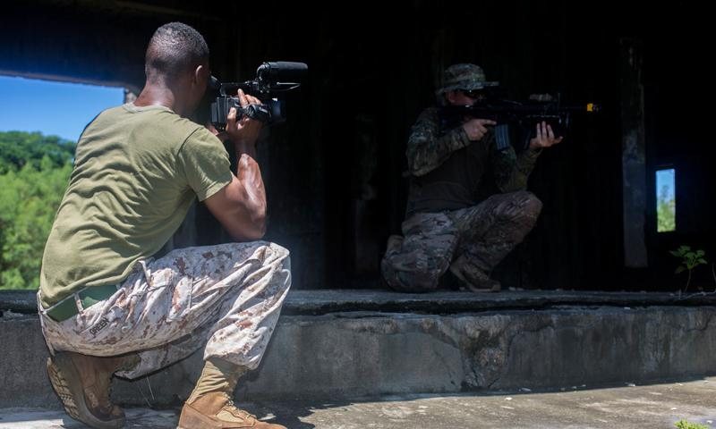 TINIAN, North Marianas Islands (Sept. 18, 2014) - U.S. Marine Corps Pfc. Lyman Green, combat videographer with Combat Camera Consolidated, Marine Corps Installations Pacific, records a Guam National Guardsman providing security during Valiant Shield 2014.  (U.S. Marine Corps photo by Lance Cpl. Austin Schlosser)