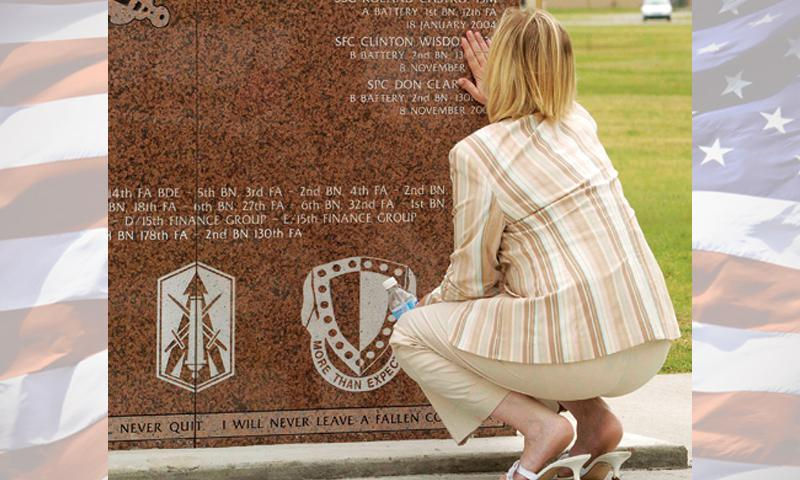 Janet Wisdom touches her husband's name carved into a war memorial in Atchison, Kan., in 2011. Individual statues commemorating the sacrifice of Sgt. 1st Class Clinton Wisdom and Spc. Don Clary are located nearby, and can be seen on page 3. Photos courtesy of Lt. Col. Austin Hamner