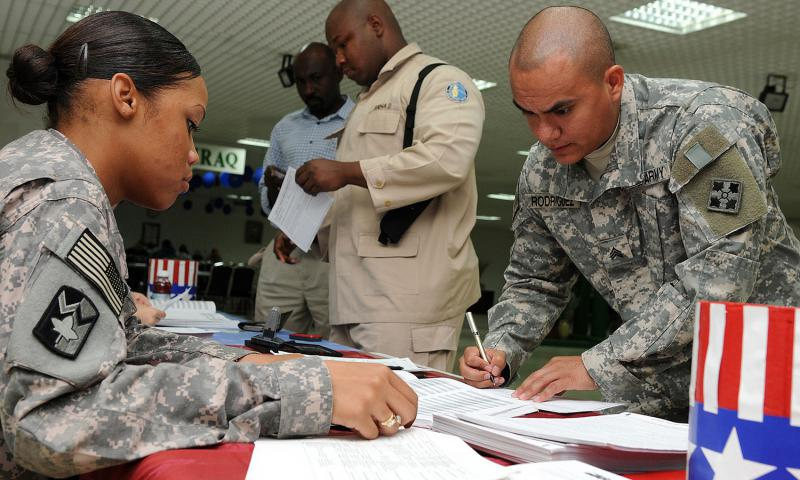 U.S. Army Pfc. Chyna Williams, from Crestview, Fla., assists Sgt. Charles Rodriguez, from Chicago, Ill., complete an absentee ballot at Camp As Sayliyah, Qatar, Oct. 16, 2008. Dustin Senger/U.S. Army