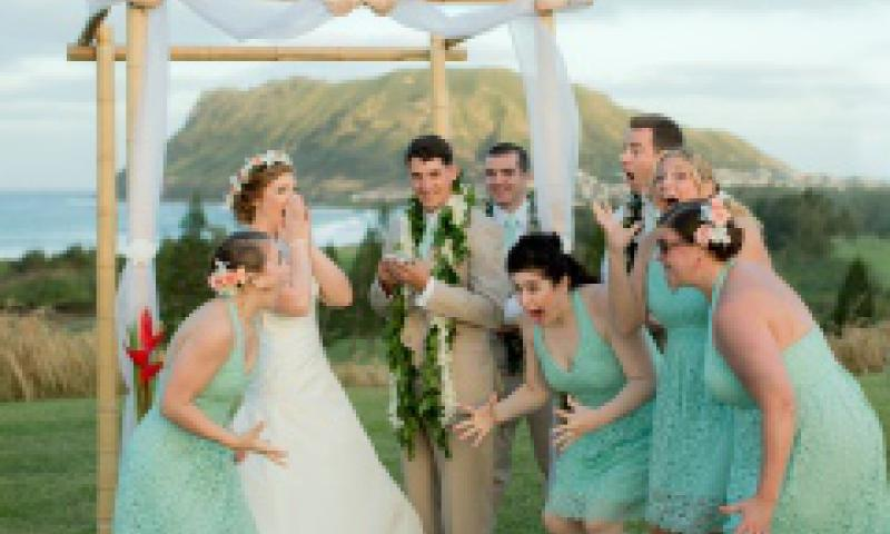 This Sunday, Dec. 28, 2014, photo provided by Keao's Photography shows Natalie Heimel, 2nd from left, and Edward Mallue Jr., 3rd from left, both U.S. Army captains stationed in Hawaii, reacting with their wedding party after getting a phone call from President Obama during their ceremony at Kaneohe Klipper Golf Course in Kaneohe Bay, Hawaii.