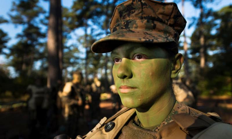 Marine Pfc. Christina Fuentes Montenegro prepares to hike to her platoon's defensive position during patrol week of Infantry Training Battalion near Camp Geiger, N.C., in October 2013. Fuentes Montenegro is one of the first three females to ever graduate from Infantry Training Battalion. The Marine general in charge of implementing a Pentagon plan to open ground combat jobs to women concluded there are benefits as well as significant risks to the proposal.  Tyler L. Main/Courtesy U.S. Marine Corps