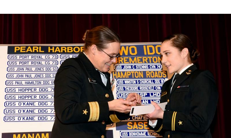Rear Adm. Cynthia M. Thebaud, commander of Expeditionary Strike Group 2, presents her Surface Warfare Officer pin to U.S. Naval Academy Midshipman 1st Class Lily Van Steenberg during Ship Selection Night in Mahan Hall on Jan. 29, 2015.  Nathan Wilkes/U.S. Navy