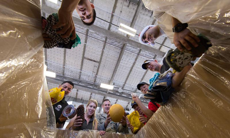 (Center) Brig. Gen. Andrew Toth, 36th Wing Group commander, and volunteers throughout the local community place relief items into a box while sorting donations for Operation Christmas Drop at Andersen Air Force Base, Guam, Dec. 5, 2015.  (U.S. Air Force photo by Osakabe Yasuo)