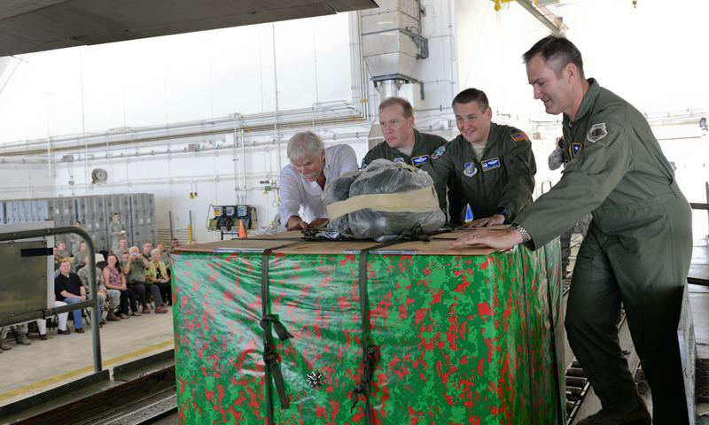 Leadership from Team Andersen, Yokota Air Base, Japan, the 515th Air Mobility Operations Wing, from Joint Base Pearl Harbor-Hickam, Hawaii, and Bruce Best, event guest speaker, push the first box onto a C-130 Hercules during the Push Ceremony, Dec. 9, 2014 at Andersen Air Force Base, Guam.  (U.S. Air Force photo by Staff Sgt. Robert Hicks)