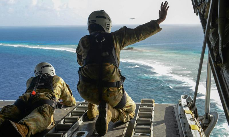 Cpl. Teome Matamua and Sgt. Phillip McIllvaney, Australian Army 176th Air Dispatch Squadron loadmasters, wave to islanders in the Federated States of Micronesia from the back of a C-130J Hercules after delivering donated goods and critical supplies to the islanders Dec. 8, 2015, during Operation Christmas Drop. The 2015 Christmas Drop missions mark the first time the event includes trilateral air support from the Japanese Air Self-Defense Force and RAAF. (U.S. Air Force photo/Staff Sgt. Katrina Brisbin)