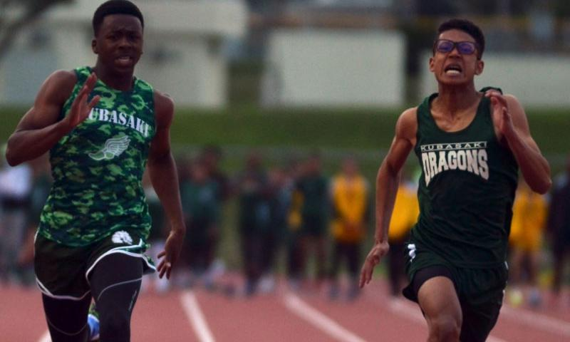 Kubasaki sophomore Mahlik Francis and senior Takao Elliot run side-by-side toward the finish of the 100 in Friday's Okinawa season-opening track and field meet. Francis won in 11.46 seconds.    Dave Ornauer/Stars and Stripes