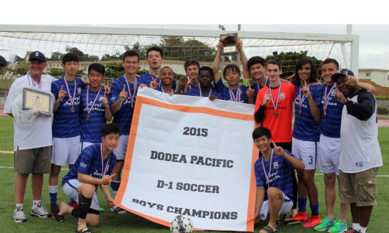 Banner time for the Falcons. Seoul American's boys soccer team gathers around the banner and displays the championship hardware. Marie Obsuna/Special to Stars and Stripes