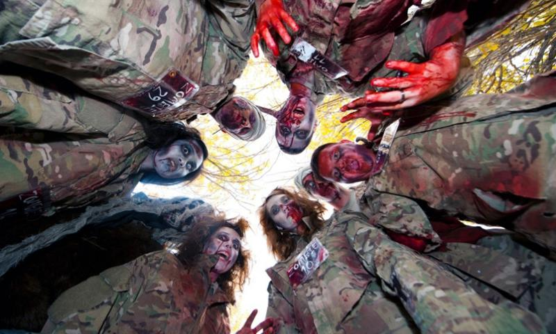 "Zombies made of simulated undead military prepare to eat their latest victim at Transit Center Manas, Kyrgyzstan, on Oct. 31, 2013. The ""zombies"" were servicemember volunteers dressed up for the Transit Center celebration of Halloween for a ""zombie run"" in Frunze Forest.   Robert Barnett/U.S. Air Force"