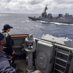 PHILIPPINE SEA (Feb. 28, 2018) Cmdr. Leroy Mitchell, commanding officer of the Arleigh Burke-class guided-missile destroyer USS Benfold (DDG 65), and Ensign Nancy Smith, from Asheville, North Carolina observe as Japanese Maritime Self-defense Force Akizuki-class destroyer JS Fuyuzuki (DD 118) sails alongside during a close quarters maneuvering exercise. (U.S. Navy photo by Mass Communication Specialist 1st Class Benjamin Dobbs/ Released)