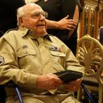Staff Sgt. Edward Mims, 83, smiles and holds his Purple Heart Medal as well-wishers thank him for his service following a ceremony in his honor at the The Villages, a retirement community in Florida, Feb. 23, 2018. Mims was awarded the medal nearly 74 years after being wounded in World War II while serving as a top turret gunner on a B-24 Liberator bomber. Fort Stewart garrison command team Col. Jason Wolter and Command Sgt. Maj. Marty Conroy present the veteran his medal. (U.S. Army photo by Kevin Larson)