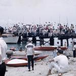 In this historic photo, people crowd the Merizo pier and shore to watch festivities during Malesso' Fiestan Tasi. The festival is still held annually and includes boat races and other water sports, cultural displays and carnival concessions. Photo by Robert Delf/Guam Museum