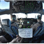 """Capt. Brandon Leigh, left, and Capt. Jeff Pecora of the 817th Expeditionary Airlift Squadron Detachment 1 based out of Manas Transition Center, Kyrgyzstan, pilot a C-17 Globemaster III carrying about 150 troops from 1st Battalion, 294th Infantry Regiment, Guam Army National Guard, from Kabul, Afghanistan. Holding the """"Going Home Task Force Guam"""" sign is Air Force Staff Sgt. Jeremy Nallay. Photo by Eddie Siguenza/U.S. Army National Guard"""