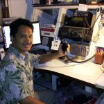 Manny Hechanova mans the radio on the University of Guam campus that connects isolated Pacific islands with the outside world. A five-person team offers daily news and weather reports, and help in emergencies, as well as coordinates between islanders and U.S. Air Force pilots during Operation Christmas Drop. Photo courtesy of Manny Hechanova.