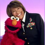 """Defense Health Agency Director Vice Admiral Raquel """"Rocky"""" Bono joined Sesame Street's Elmo to record a welcome video for the new provider section of the Sesame Street for Military Families website. (Photo by MHS Communications)"""