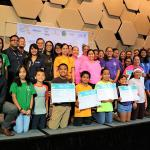 """Dee Hernandez, GVB Cultural Heritage Officer, (standing far left) and Nico Fujikawa, GVB Acting Director of Tourism Research (kneeling, front, far left) gather for a photo on stage with elementary and middle school students, advisors and teachers, representing the 500 newest members to the Håfa Adai Pledge program at the Tourism Education Council's (TEC) The Power of """"I"""": Inspire, Initiate, Innovate Islan Ideas Youth Xpo 2018 on Wednesday, February 28, 2018."""