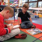 """Zachary Smith, left, and Nicholas Von Eicken, second-graders at Ramstein Elementary School take turns reading and answering questions about a story during a """"cooperative buddy"""" reading activity. The Department of Defense Education Activity is investing much time and money into its early literacy program, including implementing a new time-intensive reading assessment for more than 30,000 students in kindergarten through third grade."""